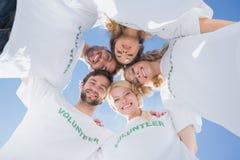 Voluntarios felices que forman un grupo contra el cielo azul Fotos de archivo libres de regalías