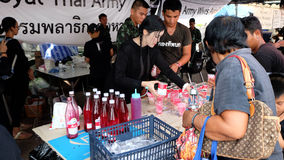 Voluntarios que dan bebidas libres a los deudos en el palacio magnífico en Bangkok Fotos de archivo libres de regalías