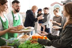 Voluntarios que dan la comida a la gente pobre fotografía de archivo