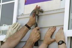 Voluntarios que instalan Sidiing en una nueva casa Imagenes de archivo