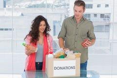 Voluntarios que sacan la comida de la caja de las donaciones Fotografía de archivo libre de regalías