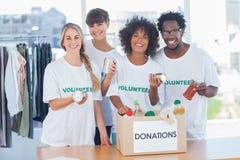 Voluntarios que sacan la comida de una caja de la donación imagenes de archivo