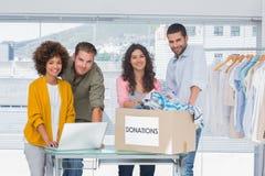 Voluntarios que usan un ordenador portátil y tomando la ropa de una caja de la donación Fotografía de archivo libre de regalías