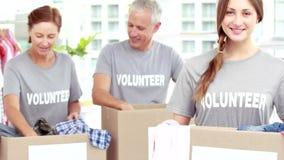 Voluntarios sonrientes de los amigos que separan la ropa almacen de metraje de vídeo