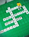 Volunteer. Key words on game boards and miniature people Stock Photos