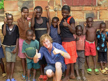 Volunteer aid relief worker having fun teaching African children thumbs up