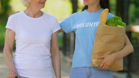 Volunteer bringing food to old disabled lady with cane, walking in hospital park. Stock footage stock video