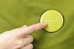 Volunteer button. Finger pointing to green round volunteer button Royalty Free Stock Image