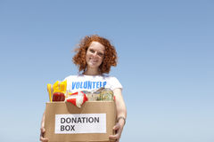 Volunteer carrying food donation box Stock Image