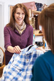 Volunteer In Charity Shop With Customer. Buying Clothes Royalty Free Stock Images