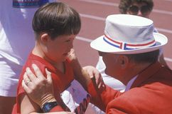 Volunteer coaching handicapped young athlete Stock Images