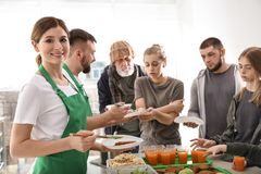 Volunteer with colleague giving food to poor people. Indoors royalty free stock photo