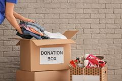 Volunteer collecting clothes into donation boxes. Indoors stock image