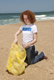 Volunteer collecting garbage on beach Stock Photo