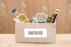 Volunteer with donation box with food stuffs on wooden background stock images