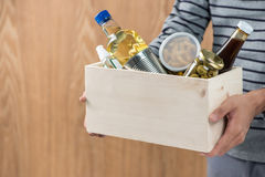Volunteer with donation box with food stuffs on wooden backgroun Stock Photography