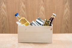 Volunteer with donation box with food stuffs on wooden backgroun Royalty Free Stock Image
