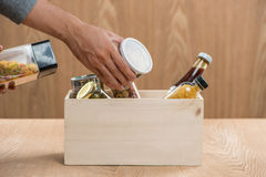 Volunteer with donation box with food stuffs on wooden backgroun Stock Images
