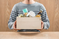 Volunteer with donation box with food stuffs on wooden backgroun. D Royalty Free Stock Photography