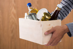 Volunteer with donation box with foodstuffs on wooden background Royalty Free Stock Photos