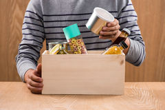 Volunteer with donation box with foodstuffs on wooden background Stock Photos