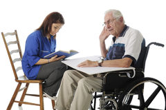 Volunteer with the Elderly. An attractive teen volunteer reading to a hard-of-hearing senior men in a wheelchair. On a white background stock photos