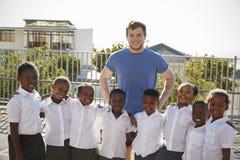 Volunteer and elementary school kids in playground, portrait Stock Image