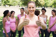 Volunteer gesturing thumbs up at breast cancer campaign Stock Images