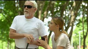 Volunteer girl helping old blind man stand up and they going for walk along park. Stock footage stock video