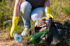 Volunteer girl in yellow gloves collects garbage Royalty Free Stock Photography