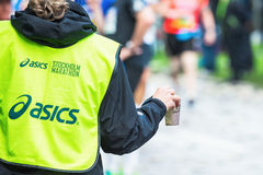 Volunteer gives out mugs with water in a depot in the ASICS Stoc Stock Photography