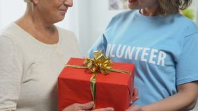 Volunteer giving birthday gift to pensioner, charity concept, financial support