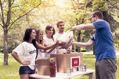 Volunteer group receives food donation. Volunteer group of young adult receives food donation in a public park Stock Images