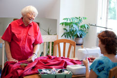 Volunteer helping a senior. Volunteer helping senior with sewing project Royalty Free Stock Photography