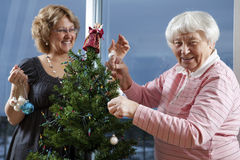 Volunteer helping senior decorate her Christmas Tr Royalty Free Stock Image