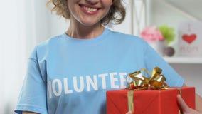 Volunteer holding presents for orphaned children, charity holidays, sponsorship