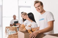 Volunteer holding teddy bear and box stock images