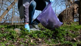 A volunteer man collects trash in a plastic bag in a city park