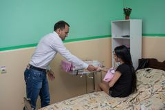 Volunteer man donating clothes for babies in the maternity hospital during children protection day. In Ukraine Stock Image