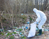 Volunteer man in white protective clothing collects garbage Royalty Free Stock Images