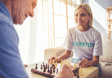 Volunteer and old people. Beautiful young girl-volunteer and handsome old men are playing chess and smiling stock photos