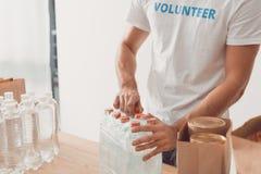 Volunteer opening pack of water bottles Royalty Free Stock Photos