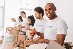 Volunteer packing food into bag. African american volunteer packing food into bags with muriethnic group of colleagues Royalty Free Stock Images