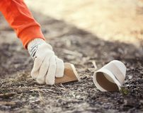 Volunteer picking up litter from sand. Closeup Royalty Free Stock Image