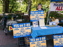 Volunteer poses with Yes on 2-89 sign at Farmers Market in Corva Stock Photography