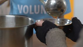 Volunteer pouring soup for homeless person in social support center, assistance. Stock footage stock video footage