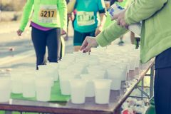 Volunteer preparing and distrubuting water to competitors. Royalty Free Stock Photos