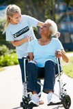 Volunteer Pushing Senior Woman In Wheelchair Stock Image