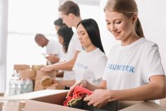 Volunteer putting clothes into box Royalty Free Stock Photo