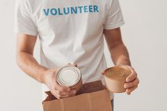 Volunteer putting tin cans in paper bag Royalty Free Stock Photos